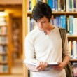 Stock Photo: Serious student reading a book