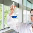 Female science student holding a blue liquid — Stock Photo