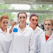 Portrait of lab partners posing with a flask — Stock Photo
