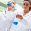 Portrait of smiling scientists pouring liquid into a flask — Stock Photo