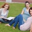 Young women sitting on the lawn — Stock Photo