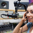 Royalty-Free Stock Photo: Young radio host putting her headphones on