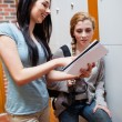 Portrait of a student showing her notes to her friend — Stock Photo #11192745