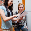Portrait of a student showing her notes to her friend — Stock Photo