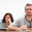 Smiling handsome student sitting — Stock Photo