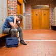 Foto Stock: Sad student sitting on bench