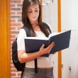 Stock Photo: Portrait of a smiling student reading a book