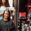 Stock Photo: Portrait of hairdresser showing to her customer her new haircu