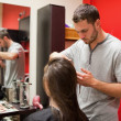 Foto Stock: Male hairdresser cutting hair