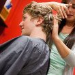 Portrait of a serious woman cutting a man's hair — Stock Photo