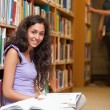 Stock Photo: Portrait of a young female student with a book