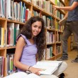 Portrait of a student with a book while her classmate is choosin - Stock Photo