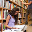 Stock Photo: Portrait of a student reading a book while her classmate is choo