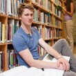 Portrait of a male student with books while his classmate is rea — Stock Photo