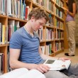 Portrait of a male student reading books while his classmate is - Photo