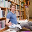 Male student doing research while his classmate is reading - Photo