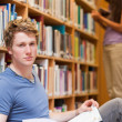 Portrait of a handsome student posing with a book while his clas - Stockfoto