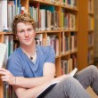 Handsome student picking a book - Stockfoto