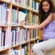 Portrait of a cute female student choosing a book — Stock Photo