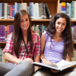 Portrait of smiling female students with a book — Stock Photo