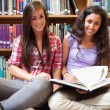 Smiling female students with a book — Stockfoto