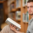 Serious male student holding a book — Stock Photo