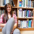Smiling student sitting against shelves — ストック写真