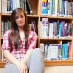 Student sitting against shelves — Stock Photo