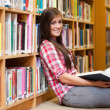 Stock Photo: Smiling young female student holding book