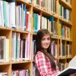 Stock Photo: Portrait of a young female student holding a book