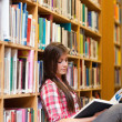 Stock Photo: Portrait of young female student reading book