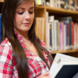 Portrait of a smiling female student reading - Photo