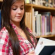 Stock Photo: Portrait of smiling female student reading