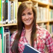 Smiling female student holding a book - Stockfoto