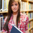 Portrait of a cute female student holding a book - Photo