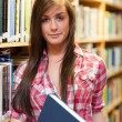 Portrait of a cute female student holding a book - Stockfoto
