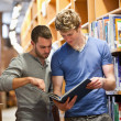 Portrait of male students looking at a book - Stockfoto