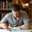 Stock Photo: Male student researching with book