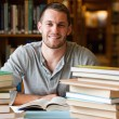 Smiling student surrounded by books — Stock Photo #11193572