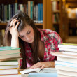 Focused student surrounded by books — Stock Photo