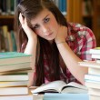 Stock Photo: Depressed student surrounded by books