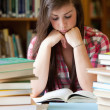 Studious woman surrounded by books — Stock Photo