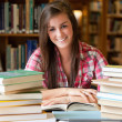 Smiling student having a lot to read — Stock Photo