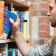 Portrait of a male student picking a book — Stockfoto