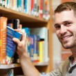 Foto Stock: Smiling male student picking a book