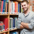 Portrait of a smiling male student leaning on a shelf — Foto Stock