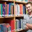 Smiling male student leaning on a shelf — Stock Photo