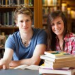 Smiling students surrounded by books — Stock Photo