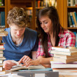 Stock Photo: Serious students looking at a book