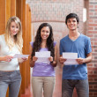 Smiling students holding a piece of paper — Stock Photo